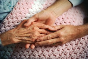Senior woman's hands being held